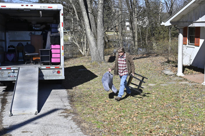 Ray Smith helps to move the furniture from the home of his friend Kelly Sparrow as the rising Kentucky River inches closer Tuesday, March 2, 2021, in Frankfort, Ky. (AP Photo/Timothy D. Easley)