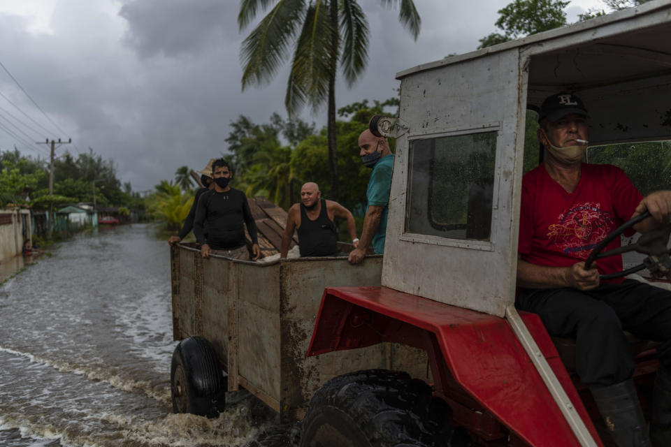 A man drives a tractor through a street flooded by rain brought on by Hurricane Ida, in Guanimar, Artemisa province, Cuba, Saturday Aug. 28, 2021. (AP Photo/Ramon Espinosa)