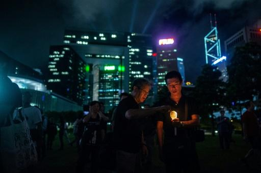 People light up candles at a memorial event in Hong Kong to mark the first anniversary of the death of late Chinese Nobel dissident Liu Xiaobo