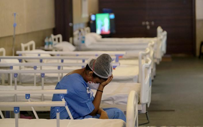 A nurse rests in a makeshift ward at an emergency Covid-19 care center in New Dehli - T. Narayan/Bloomberg