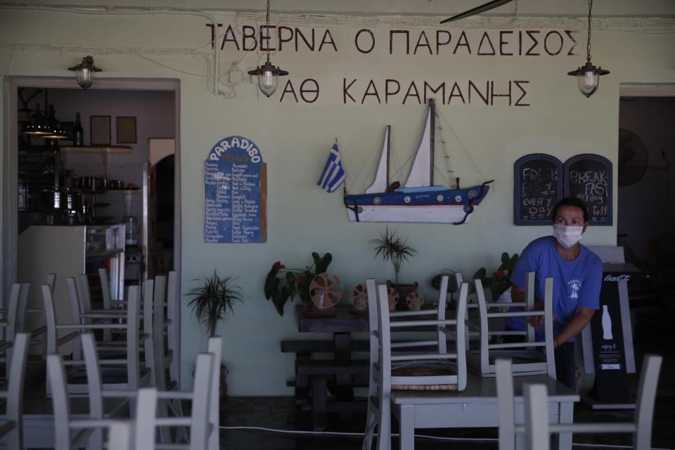 A worker places chairs at a tavern in Plaka beach, on the Aegean island of Naxos, Greece, Wednesday, May 12, 2021. With debts piling up, southern European countries are racing to reopen their tourism services despite delays in rolling out a planned EU-wide travel pass. Greece Friday became the latest country to open up its vacation season as it dismantles lockdown restrictions and focuses its vaccination program on the islands. (AP Photo/Thanassis Stavrakis)
