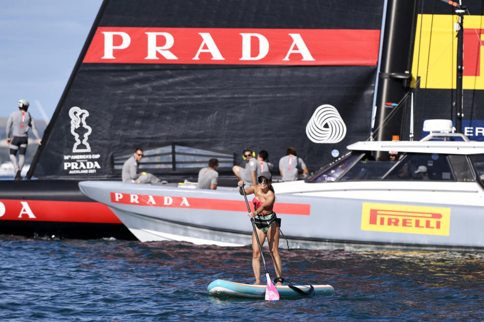 A fan on a paddle board paddles around Italy's Luna Rossa as they and Team New Zealand wait during a postponement of race 7 of the America's Cup on Auckland's Waitemata Harbour, New Zealand, Sunday, March 14, 2021. (Chris Cameron/Photosport via AP)