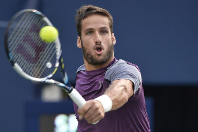 Feliciano Lopez, of Spain, retuns to Milos Raonic, of Canada, at the Rogers Cup tennis tournament, Friday, Aug. 8, 2014 in Toronto. (AP Photo/The Canadian Press, Nathan Denette)