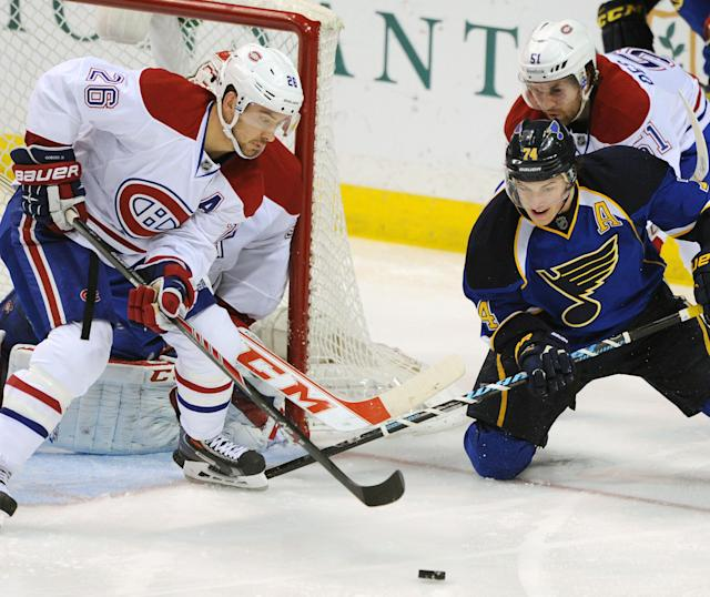 Montreal Canadiens' Josh Gorges (26) and Raphael Diaz (51), of Switzerland, defend against St. Louis Blues' T.J. Oshie (74) during the second period of an NHL hockey game on Thursday, Dec. 19, 2013, in St. Louis. (AP Photo/Bill Boyce)