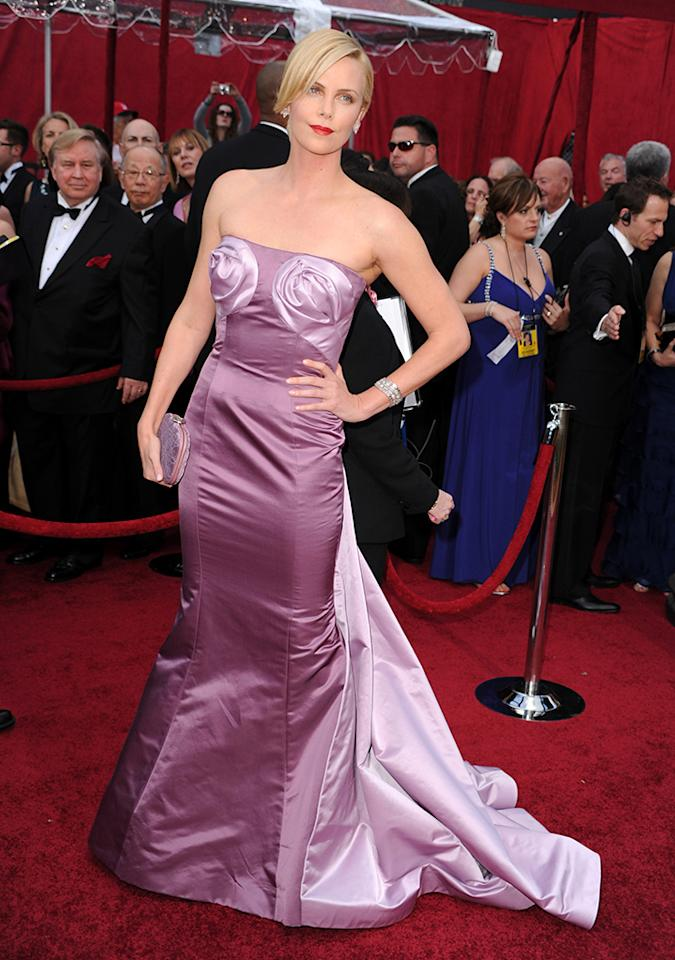 "Charlize Theron, 2010. Dior Haute Couture with pasties -- who knew? At least, that was the effect that the leggy Theron created in her mauve strapless number with two strategically placed satin roses and a crisscrossed tail in lilac. The gown, by John Galliano for Christian Dior, got some hate, but the actress gamely said in response to critics, ""I just loved this dress."" Maybe it needed a couple of tassels."