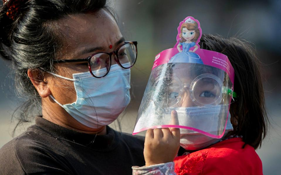 A Nepalese woman and her daughter wearing face masks at the Rato Machindranath chariot festival in Lalitpur, Nepal - Niranjan Shrestha / AP