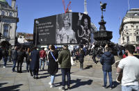 People observe a minute's silence for Britain's Prince Philip at Piccadilly Circus in London Saturday, April 17, 2021. Prince Philip, husband of Queen Elizabeth II, died Friday April 9 aged 99. His funeral service is taking place at St. George's Chapel inside Windsor Castle Saturday. (AP Photo/Rui Vieira)
