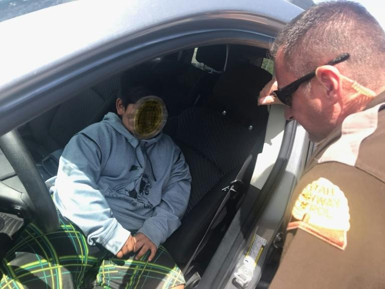 An officer speaks to a five-year-old boy pulled over after driving down the highway in Utah on May 4, in a photo released by the Utah Highway Patrol (AFP Photo/Handout)