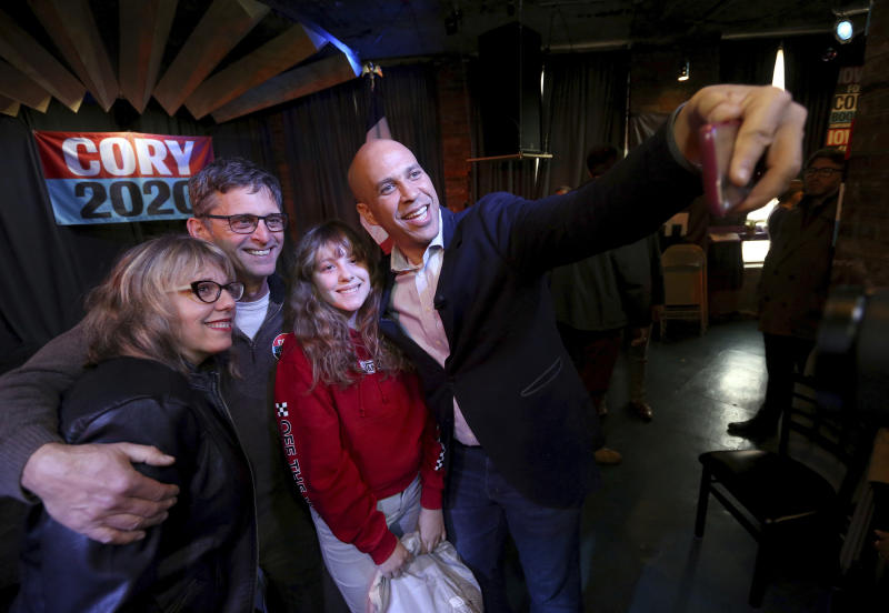 Democratic presidential candidate Sen. Cory Booker, D-N.J., takes a selfie with Mary Bichell, from left, her husband, Ken, and daughter, Maddie, 12, during an event at Smokestack in Dubuque, Iowa, on Sunday, Dec. 8, 2019. (Jessica Reilly/Telegraph Herald via AP)