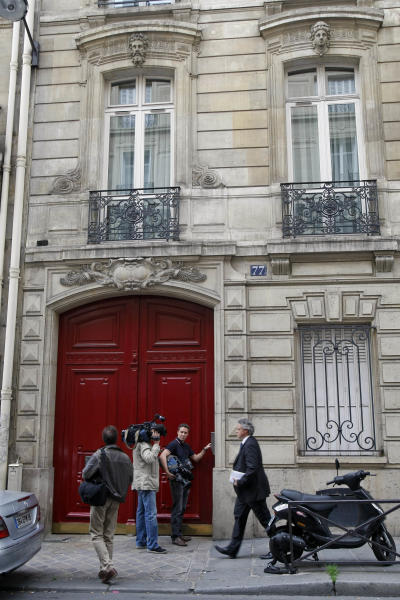 Members of the media are seen at the entrance of the building housing the offices of former French President Nicolas Sarkozy in Paris, Tuesday July 3, 2012. French investigators searched Nicolas Sarkozy's home and office on Tuesday as part of a probe into suspected illegal financing of his 2007 presidential campaign by the L'Oreal cosmetics heiress, an official said.(AP Photo/Remy de la Mauviniere)
