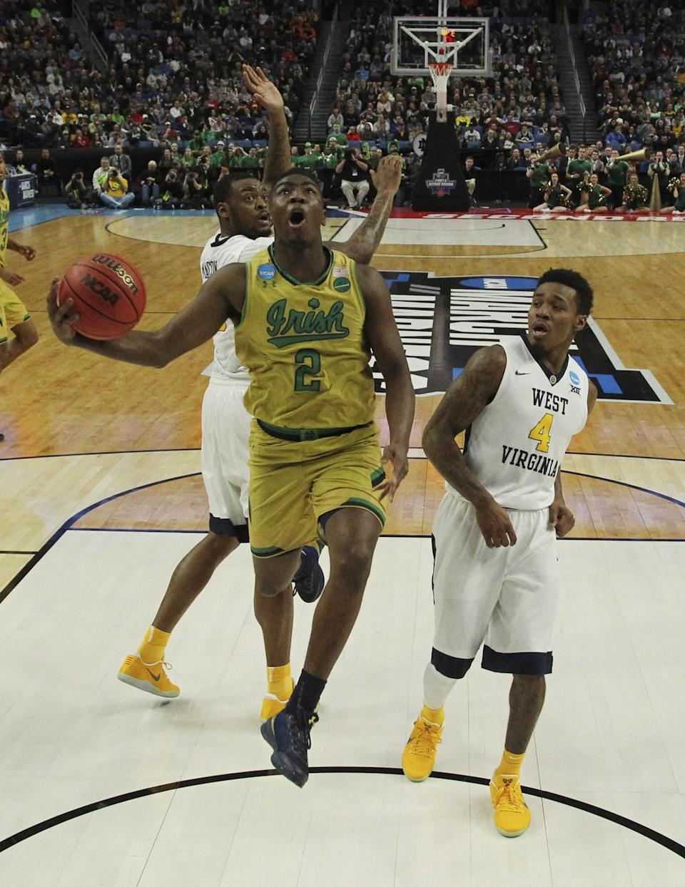 <p>Notre Dame guard Temple Gibbs (2) goes to the basket against West Virginia forward Elijah Macon (45) and guard Daxter Miles Jr. (4) during the first half of a second-round men's college basketball game in the NCAA Tournament, Saturday, March 18, 2017, in Buffalo, N.Y. (AP Photo/Bill Wippert) </p>