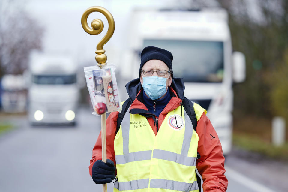 Pastor Michael Ohlemueller is standing at the motorway service station Wonnegau near Worms, Germany, with a crosier with chocolate Santa Claus and apple in a bag, which he wants to distribute as a gift to truck drivers. The action is intended as a thank you and appreciation for the drivers' work. ( Uwe Anspach/dpa via AP)