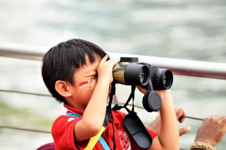 Small child with big binoculars and painted face