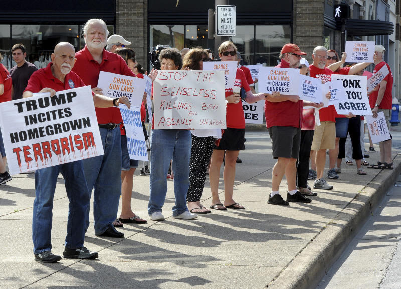 People hold signs protesting gun violence during a rally in front of the United Building in Charleston, W.V., Saturday, Aug. 17, 2019. (Chris Dorst/Charleston Gazette-Mail via AP)
