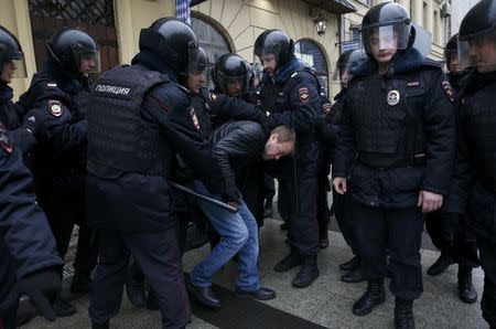 Policemen detain a man during an anti-government protest in Moscow