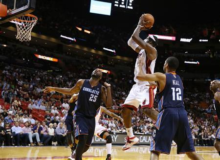 Mar 3, 2014; Miami, FL, USA; Miami Heat small forward LeBron James (6) makes a shot as Charlotte Bobcats center Al Jefferson (25) and shooting guard Gary Neal (12) look on in the second half at American Airlines Arena. The Heat won 124-107. Robert Mayer-USA TODAY Sports