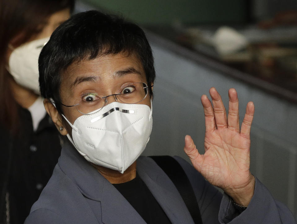 <p>Rappler CEO and Executive Editor Maria Ressa, wearing a protective mask, waves to the media before attending a court hearing at Manila Regional Trial Court, Philippines on Monday June 15, 2020. Ressa's verdict is expected to be announced Monday for a cyber libel case. (AP Photo/Aaron Favila)</p>