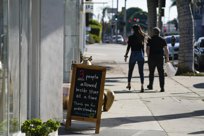 A sign restricting the number of customers stands outside of a shop Wednesday, Nov. 18, 2020, in the West Hollywood area of Los Angeles. Los Angeles County imposed new restrictions on businesses Tuesday and is readying plans for a mandatory curfew for all but essential workers if coronavirus cases keep spiking. (AP Photo/Ashley Landis)
