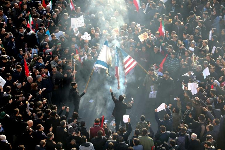 Iranians set a US and an Israeli flag on fire during a funeral procession for slain military commander Qasem Soleimani in Tehran on January 6 (AFP Photo/Atta KENARE)