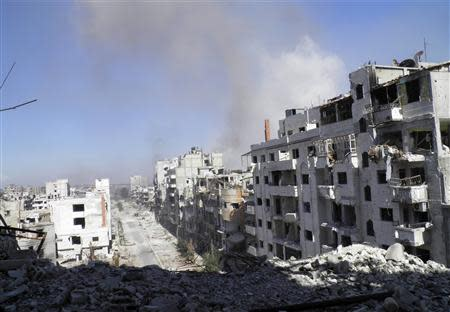 Smoke rises from buildings after what activists say was an air strike by forces loyal to Syrian President Bashar Al-Assad in Homs