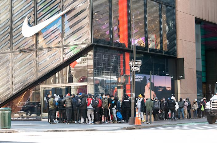 NEW YORK, NEW YORK - NOVEMBER 23: People stand in line outside the Nike store on Fifth Avenue on November 23, 2020 in New York City. The pandemic has caused long-term repercussions throughout the tourism and entertainment industries, including temporary and permanent closures of historic and iconic venues, costing the city and businesses billions in revenue. (Photo by Noam Galai/Getty Images)
