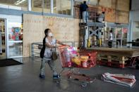 Workers board up windows of a supermarket in Mexico's eastern state of Veracruz to prevent damage from approaching Hurricane Grace