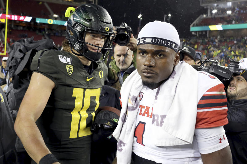 Oregon quarterback Justin Herbert (10) shakes hands with Utah quarterback Tyler Huntley (1) at midfield at the end of the Pac-12 Conference championship NCAA college football game in Santa Clara, Calif., Friday, Dec. 6, 2018. Oregon won 37-15. (AP Photo/Daniel Alvarez)