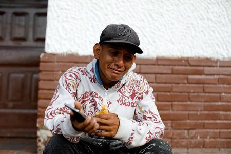 FILE PHOTO: Luis Pena, an undocumented Venezuelan migrant, cries after he received a voice message from his mother on the cellphone of a travel companion, while resting next to the road between Pamplona and La Laguna, near Mutiscua, Colombia August 28, 2018. REUTERS/Carlos Garcia Rawlins/File Photo