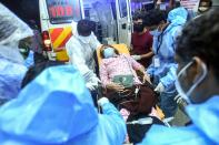 Health workers transfer an inured passenger on a stretcher to take her inside a hospital in Kozhikode, Kerela, after an Air India Express jet crashed by overshooting the runway at Calicut International Airport, on August 7, 2020. - At least 19 people died when a passenger jet skidded off the runway after landing in heavy rain in India, police said on August 7. (Photo by - / AFP) (Photo by -/AFP via Getty Images)