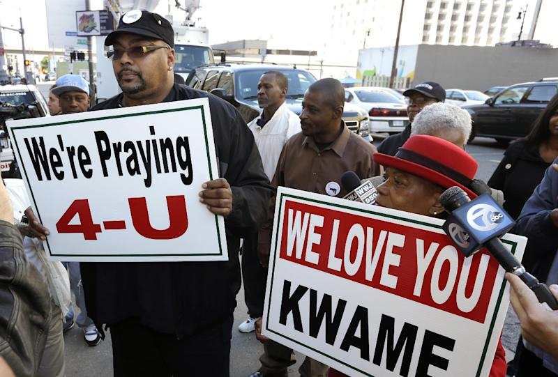 Malik Shabazz, left, and Wanda Redmond show their support for former Detroit Mayor Kwame Kilpatrick outside federal court in Detroit, Thursday, Oct. 10, 2013. Kilpatrick was sentenced Thursday to 28 years in prison, one of the longest recent punishments for public corruption in the United States. (AP Photo/Carlos Osorio)