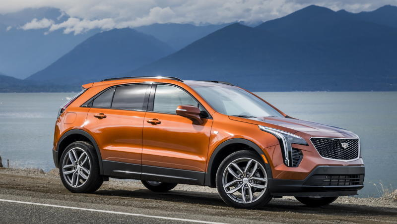An orange Cadillac XT4, a compact luxury crossover SUV, parked by a lake