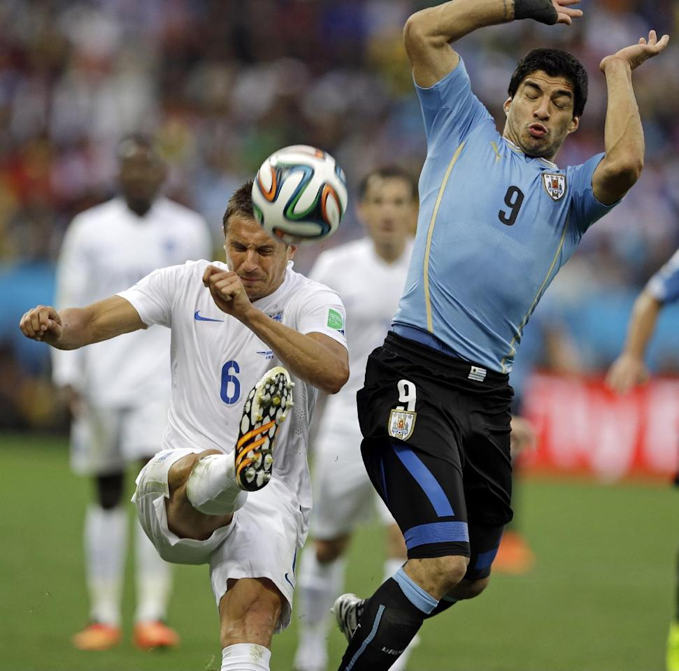 England's Phil Jagielka kicks the ball away from Uruguay's Luis Suarez during the group D World Cup soccer match between Uruguay and England at the Itaquerao Stadium in Sao Paulo, Brazil, Thursday, June 19, 2014.  (AP Photo/Kirsty Wigglesworth)