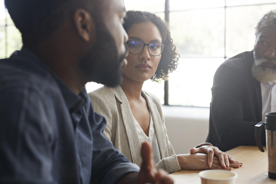 Contemplating female executive looking at male coworker while sitting by table at modern workplace