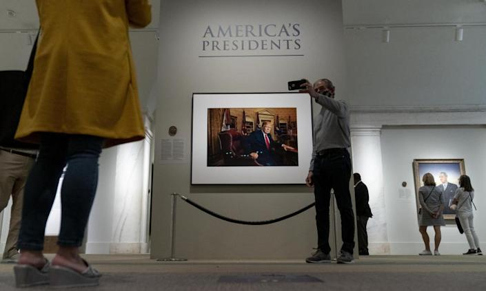 A man takes a selfie with the photo of Trump at the National Portrait Gallery.