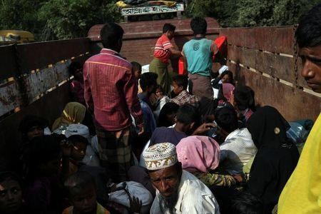 FILE PHOTO - Newly arrived Rohingya refugees sit on a truck to take them to get registered after crossing the Bangladesh-Myanmar border at a relief centre in the Teknaf area