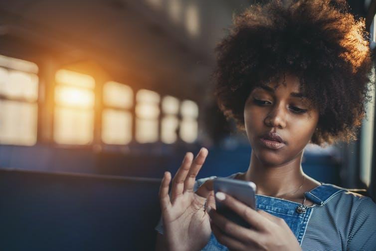 Young black woman looking at phone