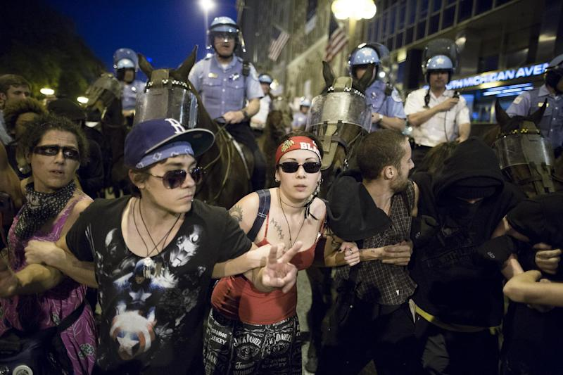 Anti-NATO protestors form a barricade in front of mounted police officers during a march, Saturday, May 19, 2012, in Chicago. On Sunday, the start of the two-day NATO summit, thousands of protesters are expected to march to the McCormick Place convention center, where NATO delegates will be meeting. (AP Photo/John Minchillo)