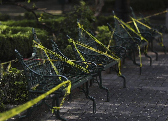 Caution tape is looped around park benches to discourage people from sitting on them in the main plaza of Coyoacan, in Mexico City, Saturday, April 4, 2020. Mexico has started taking tougher measures against the new coronavirus, but some experts warn the country is acting too late and testing too little to prevent the type of crisis unfolding across the border in the United States. (AP Photo/Fernando Llano)