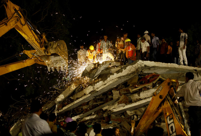Rescue workers look for trapped people after a residential building collapsed in Thane, Mumbai, India, Thursday, April 4, 2013. At least 6 persons were killed and 40 were injured when an under-construction residential building collapsed on Thursday evening according to local reports.(AP Photo/Rafiq Maqbool)