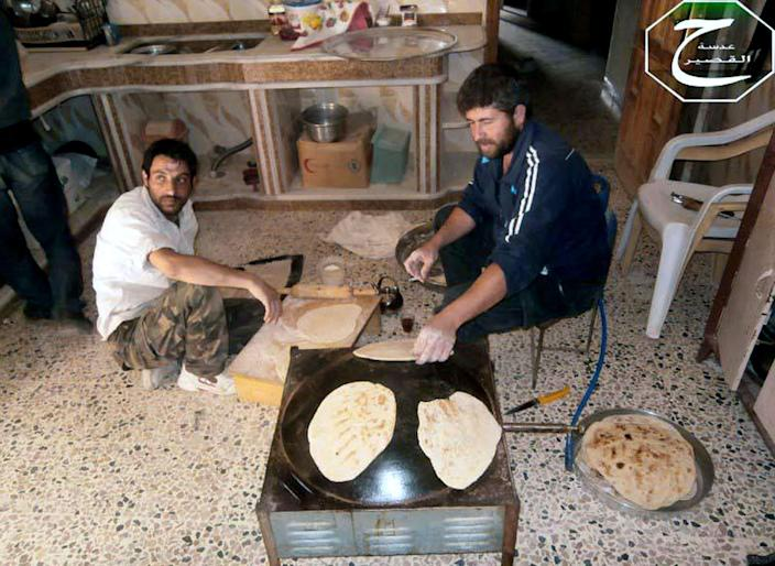 This Sunday, June 2, 2013 citizen journalism image provided by Qusair Lens, which has been authenticated based on its contents and other AP reporting, shows Syrian rebels making bread in the town of Qusair, near the Lebanon border, Homs province, Syria. Cut off for three weeks by a regime siege, doctors in the Syrian town of Qusair keep hundreds of wounded in storerooms and underground shop cellars, short on antibiotics and anesthesia, using unsterilized cloth for bandages and blowing air with pumps because there's no oxygen canisters, amid relentless shelling and sniper fire. More than a dozen have died from untreated wounds and at least 300 others need immediate evacuation, one doctor says. (AP Photo/Qusair Lens)