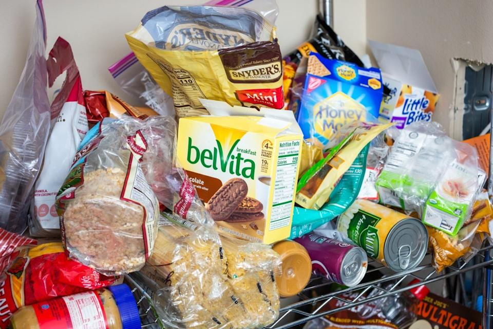 A view inside a food pantry, featuring an array of assorted food and beverage products and packages in a disorganized fashion.