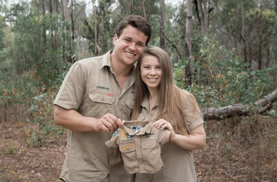 Bindi Irwin and Chandler Powell holding up a baby zookeeper outfit
