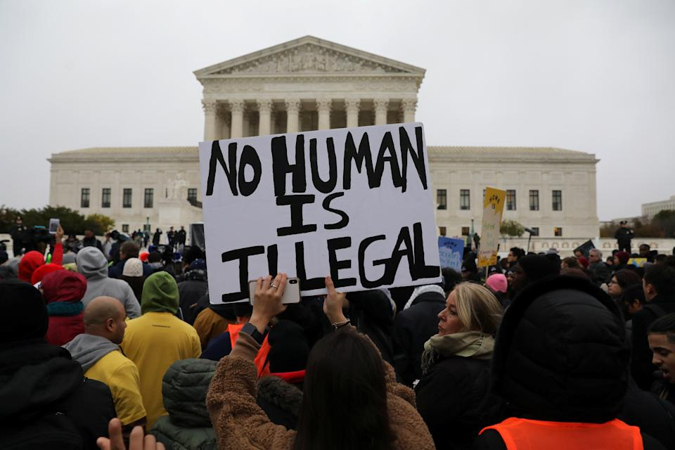 Demonstrators hold signs outside the U.S. Supreme Court