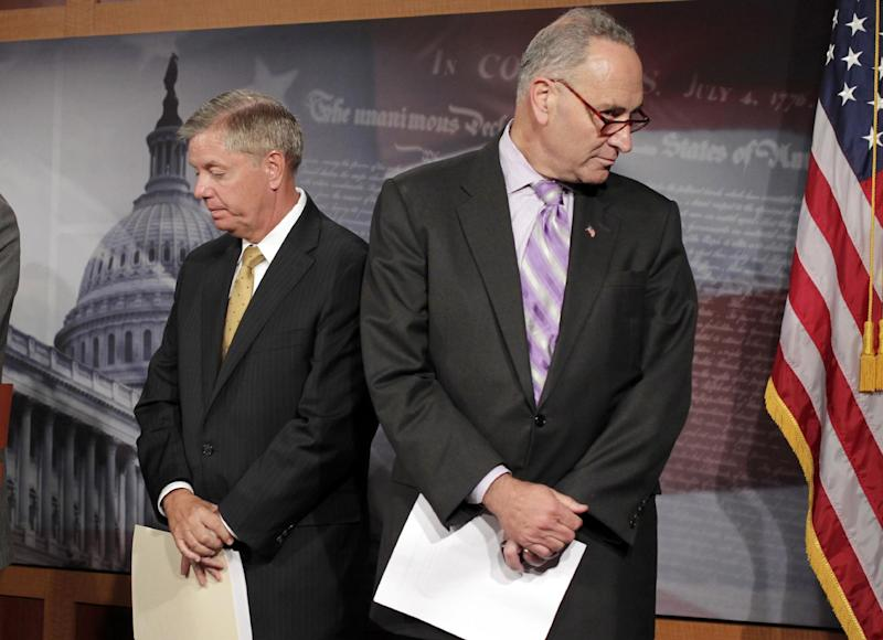 FILE - In this Oct. 12, 2011 file photo, Sen. Lindsey Graham, R-S.C., left, and Sen. Charles Schumer, D-N.Y. wait to speak at a news conference on Capitol Hill in Washington. Senators writing a comprehensive immigration bill are likely to abandon plans to institute a national ID for all workers. It proved too costly, a key senator says. Instead they are looking at expanding a little-used and error-prone  program that lets employers verify the immigration status of workers through Social Security numbers. (AP Photo/J. Scott Applewhite, File)