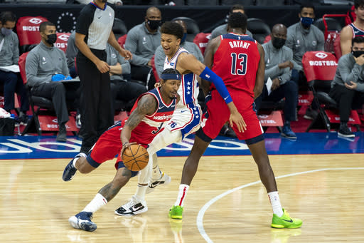 Washington Wizards guard Bradley Beal, left, makes his move on Philadelphia 76ers guard Matisse Thybulle, center, while using center Thomas Bryant, right, as a screen during the first half of an NBA basketball game, Wednesday, Jan. 6, 2021, in Philadelphia. (AP Photo/Chris Szagola)