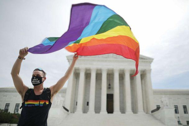 PHOTO: Joseph Fons holding a Pride Flag, stands in front of the U.S. Supreme Court building after the court ruled that LGBTQ people can not be disciplined or fired based on their sexual orientation, June 15, 2020 in Washington, DC. (Chip Somodevilla/Getty Images)