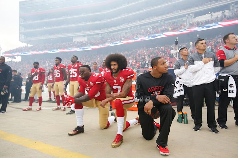 Eli Harold #58, Colin Kaepernick #7 and Eric Reid #35 of the San Francisco 49ers kneel on the sideline, during the anthem, prior to the game against the New York Jets at Levi Stadium on December 11, 2016 in Santa Clara, California.