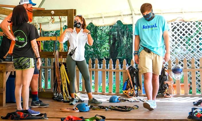 Olivia Panozzo, center, director of operations at ZipLine Hilton Head, goes over details on the harness system with employees on Tuesday, June 30, 2020 on Hilton Head Island. Before the Town off Hilton Head Island's ordinance for mandatory face coverings, employees at the outdoor adventure company were wearing face coverings, kept customers six feet apart and wear plastic face shields when checking customers gear to reduce the spread of the coronavirus.