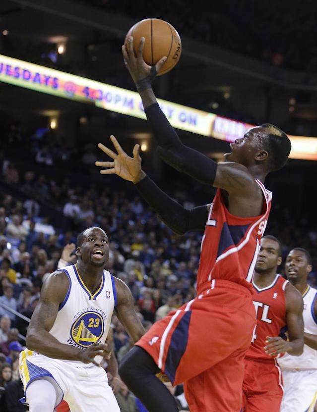 Atlanta Hawks' Dennis Schroder, right, lays up a shot in front of Golden State Warriors' Draymond Green (23) during the first half of an NBA basketball game Friday, March 7, 2014, in Oakland, Calif. (AP Photo/Ben Margot)