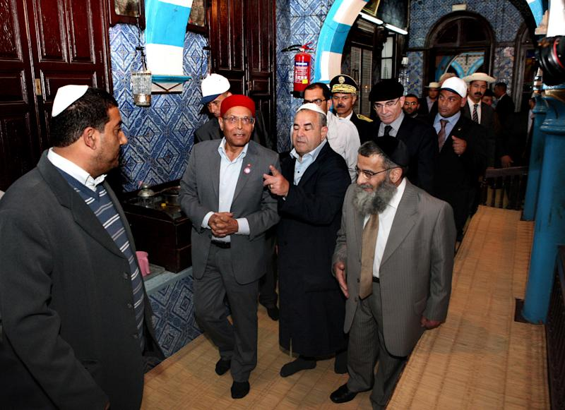President Moncef Marzouki, center, visits the synagogue on Djerba island, Tunisia Wednesday, April 11, 2012 to mark the 10th anniversary of an al-Qaida truck bomb at the synagogue that killed 21 people. It comes at a time when Tunisia's small, 1,500-strong, Jewish community is facing pressure from ultraconservative Muslim groups, after an uprising last year overthrew Tunisia's decades-old secular dictatorship. (AP Photo)